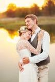 Stående av nyligen ett gift par Bröllopparet står på bakgrunden av beställningen Arkivfoto