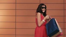 Stående av påsar för shopping för härlig ung brunettflicka hållande stock video