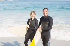 Stående av par med surfingbrädan som går på stranden Royaltyfri Bild