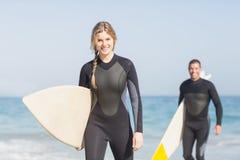 Stående av par med surfingbrädan som går på stranden Royaltyfria Foton