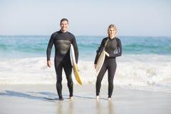 Stående av par med surfingbrädan som går på stranden Arkivfoton