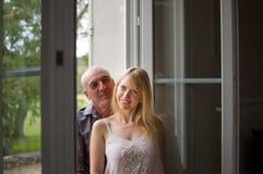 Stående av paren med ålderskillnaden som står nära öppnade Windows i rummet och ser kameran med leende Arkivfoto