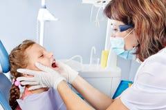 Undersökande unge för tandläkare tänder royaltyfria bilder