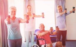 Stående av pensionärer som övar med vikter Arkivbild