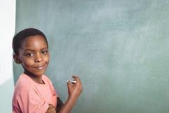 Stående av pojkeanseendet vid greenboard arkivfoton