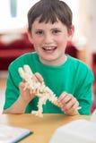 Stående av pojkedanandemodellen Dinosaur At Home arkivfoto