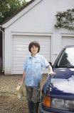 Stående av pojkeinnehavsvampen med den tvättade bilen arkivbild