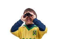 Stående av pojken med kikare över vit bakgrund Arkivfoton