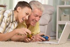 Stående av pojken och farfadern som spelar dataspelen royaltyfria bilder