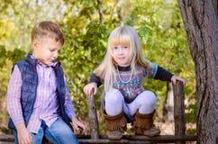 Stående av pojken och flickan i skog Arkivfoton