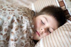 Stående av pojken som sover i sängdag Arkivfoton