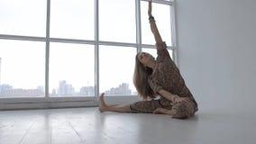 Stående av praktiserande yoga för kvinna bara i studio mot fönsterbakgrund lager videofilmer