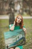 Stående av redhairflickan i grön klänning med freskomålningen i henne händer arkivfoton