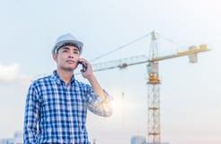 Stående av säkerhet för hjälm för arkitektkläder vit på konstruktionssi Arkivfoton