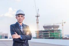 Stående av säkerhet för hjälm för arkitektkläder vit på konstruktionssi Arkivbild
