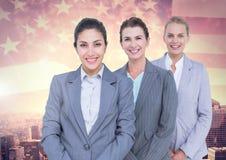 Stående av säkra affärskvinnor som står mot cityscape och amerikanska flaggan Fotografering för Bildbyråer