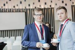 Stående av säkra affärsmän som rymmer kaffekoppar i konventcentrum Royaltyfria Foton