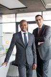 Stående av säkra affärsmän som tillsammans i regeringsställning står royaltyfri fotografi