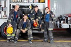Stående av säkra brandmän med lastbilen Royaltyfri Foto