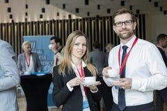 Stående av säkra koppar för kaffe för affärsfolk hållande på lobbyen i konventcentrum Arkivfoton