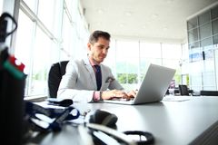 Stående av sammanträde för ung man på hans skrivbord i kontoret arkivbilder
