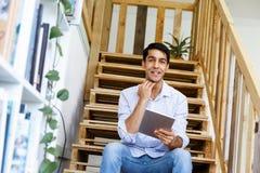 Stående av sammanträde för ung man på trappan i regeringsställning Arkivfoto