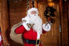 Stående av Santa Claus som rymmer hans påse och ringer en klocka det ` s Royaltyfri Foto