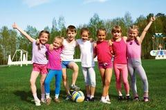 Stående av sju lilla barn med bollar Arkivbilder