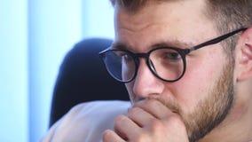 Stående av skäggiga bärande exponeringsglas för en ung man som sitter i hans kontor som arbetar på en dator Datorskärmen reflekte royaltyfria foton