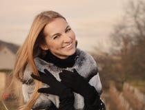 Stående av skönhetbarnet som ler bärande pälscoa för blond kvinna arkivfoto