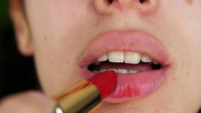 Stående av skönhetflickan som målar ineptly kanter med ljus röd läppstift Makroen som skjutas av ung kvinna, utgör kanter som app arkivfilmer