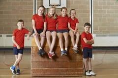 Stående av skolaidrottshallen Team Sitting On Vaulting Horse Fotografering för Bildbyråer