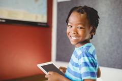 Stående av skolpojken som rymmer den digitala minnestavlan i klassrum royaltyfri fotografi
