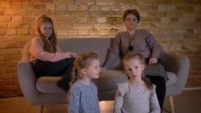 Stående av små caucasian flickor som uppmärksamt håller ögonen på film och talar med de i mysig hem- atmosfär arkivfilmer