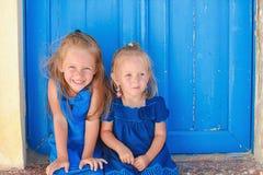Stående av små förtjusande flickor som sitter nära gammalt Fotografering för Bildbyråer