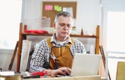 Stående av snickaresammanträde på hans seminarium och arbete med bärbara datorn Royaltyfria Foton
