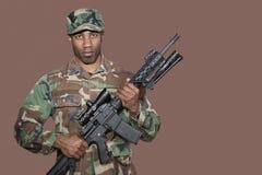 Stående av soldaten för afrikansk amerikanUSA som Marine Corps rymmer geväret för anfall M4 över brun bakgrund Royaltyfria Bilder