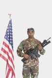 Stående av soldaten för USA Marine Corps med anseende för gevär för anfall M4 vid amerikanska flaggan över grå bakgrund royaltyfri bild