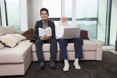 Stående av sonsonläseboken medan farfar som hemma använder bärbara datorn på soffan Royaltyfri Bild