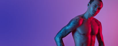 Stående av sportpassformmannen med tatuerade armar Muskulös naken torso på en rosa blå bakgrund arkivbild