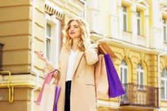 Stående av stilfullt härligt blont hår som ler flickan med shopping lycklig shopping Royaltyfri Bild