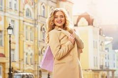 Stående av stilfullt härligt blont hår som ler flickan med shopping lycklig shopping Royaltyfri Foto