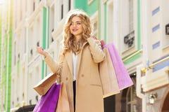 Stående av stilfullt härligt blont hår som ler flickan med shopping lycklig shopping Arkivfoton