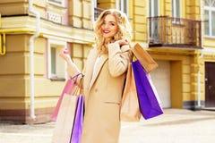 Stående av stilfullt härligt blont hår som ler flickan med shopping lycklig shopping Arkivbilder