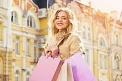 Stående av stilfullt härligt blont hår som ler flickan med shopping lycklig shopping Royaltyfria Foton