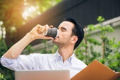 Stående av stiligt lyckat mandrinkkaffe Lyckligt avbrott för mantagandekaffe som honom sammanträde på hans arbete för bärbar dato Arkivfoto