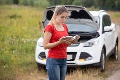 Stående av stressade läsande manuella anvisningar för ung kvinna för hennes brutna bil arkivfoton