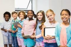 Stående av studenter som rymmer den digitala minnestavlan i klassrum arkivfoto