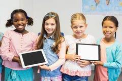 Stående av studenter som rymmer den digitala minnestavlan i klassrum royaltyfri foto