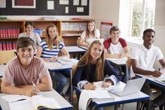 Stående av studenter som sitter på skrivbord i klassrum royaltyfria foton